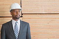 Confident African American male contractor looking away while standing in front of stacked wooden planks