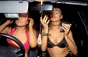 Two girls, club dancers, getting ready, putting on their make up, in their car, wearing bras and skimpy outfits, UK 2004