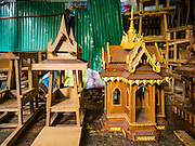 02 NOVEMBER 2016 - BANGKOK, THAILAND: A spirit house about 1/3 finished and a completed spirit house in a family owned spirit house workshop in the Ban Fuen community. There used to be 10 families making traditional spirit houses out of teak wood in Ban Fuen, a community near Wat Suttharam in the Khlong San district of Bangkok. The area has been gentrified and many of the spirit house makers have moved out, their traditional wooden Thai houses replaced by modern apartments. Now there is just one family making the elaborate spirit houses. The spirit houses are made by hand. It takes three days to make a small one and up to three weeks to make a large one. Prices start at about $90 (US) for a small one. The largest, most elaborate ones can cost over $1,000 (US). Almost every home and most commercial buildings in Thailand have a spirit house, which is a shrine to the protective spirit of a the land. Spirit houses are also common in Burma, Cambodia, and Laos.        PHOTO BY JACK KURTZ