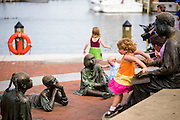 """Annapolis, Maryland - June 05, 2016: Emery DeMartino, 4, from McLean, Va., plays on the Kunta Kinte-Alex Haley Memorial statue in historic Annapolis Sunday June 5th, 2016.  Earlier that day a perigean spring tide brought some of the highest water levels of the year to the coastal town and partially flooded the park.<br /> <br /> <br /> A perigean spring tide brings nuisance flooding to Annapolis, Md. These phenomena -- colloquially know as a """"King Tides"""" -- happen three to four times a year and create the highest tides for coastal areas, except when storms aren't a factor. Annapolis is extremely susceptible to nuisance flooding anyway, but the amount of nuisance flooding has skyrocketed in the last ten years. Scientists point to climate change for this uptick. <br /> <br /> <br /> CREDIT: Matt Roth for The New York Times<br /> Assignment ID: 30191272A"""