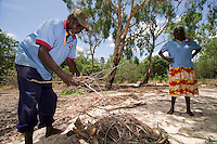 Local aboriginal Wik elders Jasper Kowearpta and Dawn Koondumbin keep an eye on the fire in which lunch of freshly caught fish is cooking in the Aurukun Wetlands, remote Cape York, far northern Queensland, Australia..