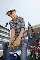 Mid adult woman holding a break hose of a logging truck
