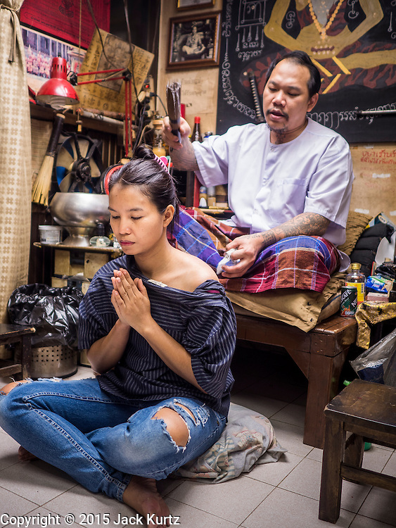 """25 MAY 2015 - BANGKOK, THAILAND:  PAT, a Thai woman getting a tattoo, gets a tattoo from AJARN NENG ONNUT in his Sak Yant tattoo parlor. Sak Yant (Thai for """"tattoos of mystical drawings"""" sak=tattoo, yantra=mystical drawing) tattoos are popular throughout Thailand, Cambodia, Laos and Myanmar. The tattoos are believed to impart magical powers to the people who have them. People get the tattoos to address specific needs. For example, a business person would get a tattoo to make his business successful, and a soldier would get a tattoo to help him in battle. The tattoos are blessed by monks or people who have magical powers. Ajarn Neng, a revered tattoo master in Bangkok, uses stainless steel needles to tattoo, other tattoo masters use bamboo needles. The tattoos are growing in popularity with tourists, but Thai religious leaders try to discourage tattoo masters from giving tourists tattoos for ornamental reasons.       PHOTO BY JACK KURTZ"""