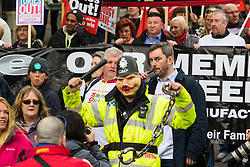 "London, April 16th 2016. A ""policeman"" wears a pig mask as thousands of people supported by trade unions and other rights organisations demonstrate against the policies of the Tory government, including austerity and perceived favouring of ""the rich"" over ""the poor""."