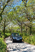 Driving 4 x 4 Range Rover car along country lane in North Devon, Southern England, UK