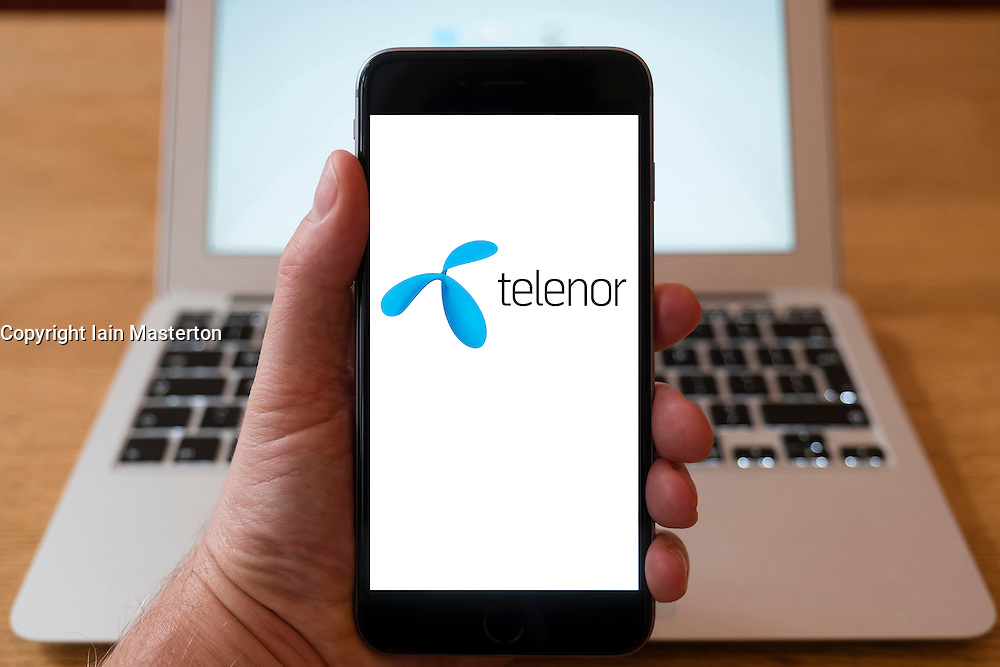 Using iPhone smartphone to display logo of Telenor , Norwegian multinational telecommunications company headquartered