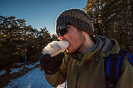 Matthew eating a chunk of snow at the top of the bushline, just before going back down to the carpark.