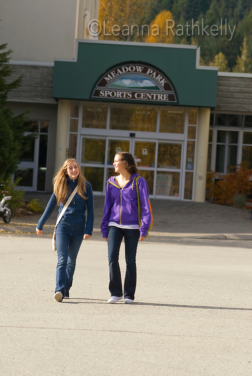 Teenage girls walk by the Meadow Park Recreation Centre in Whistler, BC, which features a hockey rink, swim pools and fitness areas.