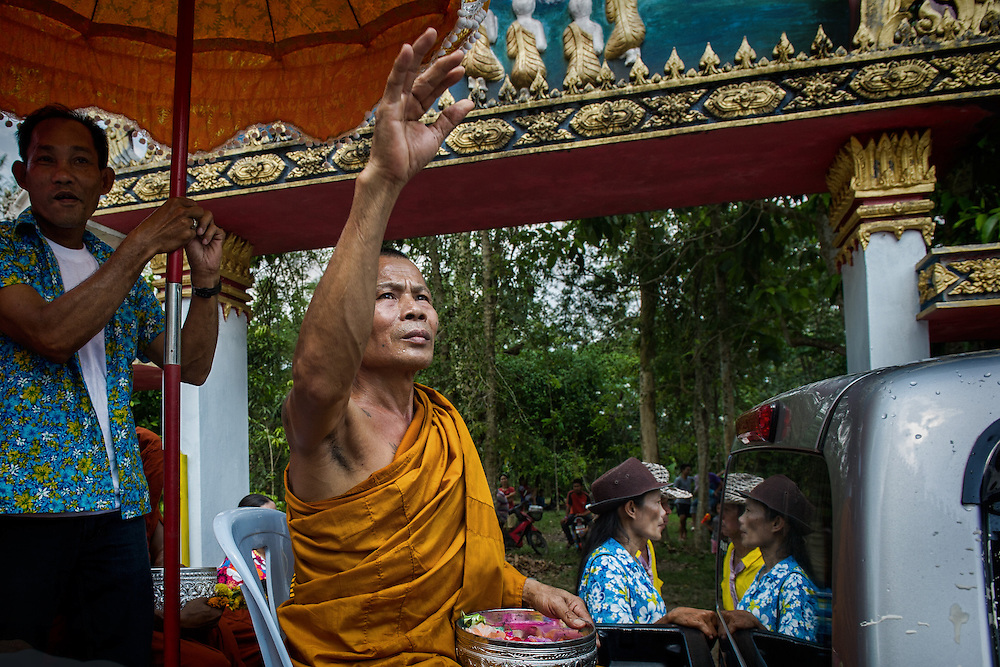 A monk throws trinkets to the congregation during Songkran in Nakhon Nayok, Thailand
