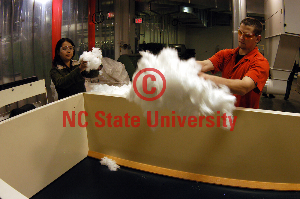 College of Textiles' students load cotton in an NCRC lab Centennial Campus.   photo by Roger Winstead