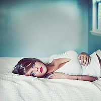 Close up of young woman with blonde hair lying alone on a bed wearing a white dress