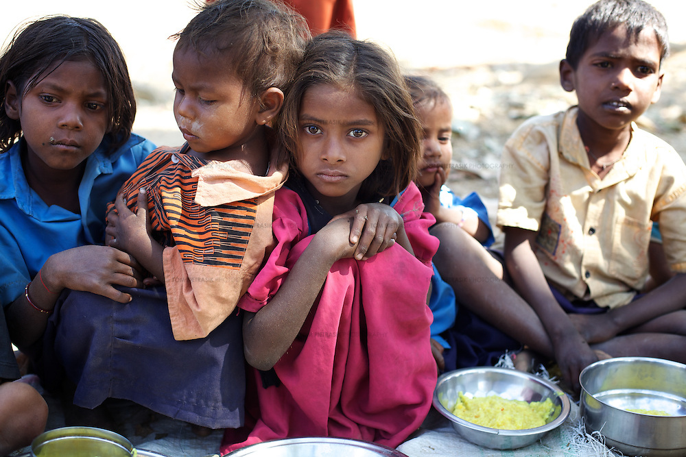 Children at the Jalhe Bogiya village Anganwadi (child-care) centre enjoy a hot lunch there six days a week. <br /> <br /> Lack of irrigation and food security lie at the root of the Maha Dalit community's problems in the village of Jalhe Bogiya. In the exploitative and divisive caste system, Maha Dalits are considered the lowest of the low. Ostracized by wider society (including the administration) illiteracy runs as high as 95 percent. Thanks to Oxfam-supported intervention, Jalhe Bogiya now has an - as yet incomplete - access-road built as part of the NREGA (National Rural Employment Guarantee Scheme). And an Oxfam-supported initiative in summer 2010 successfully lobbied the local administration to implement the provision of school midday meals which, by law is the right of every child. It is alleged that the Anganwadi (pre-school) centre administrator, syphons off food meant for young children. Jalhe Bogiya has several hand pumps supplying water but these do not work between the months of May to October. And though the village was connected to the electricity grid six months ago, power-supply is not reliable. Without land-ownership and only irregular agricultural work from which to earn an income, the Maha Dalits of Jalhe Bogiya frequently migrate in search of labour at stone breaking quarries, brick-kilns or undertake menial household work in the homes of the urban middle class in far-away cities. <br /> <br /> Photo: Tom Pietrasik<br /> Mohanpur Block, Gaya District, Bihar. India<br /> February 23rd 2011