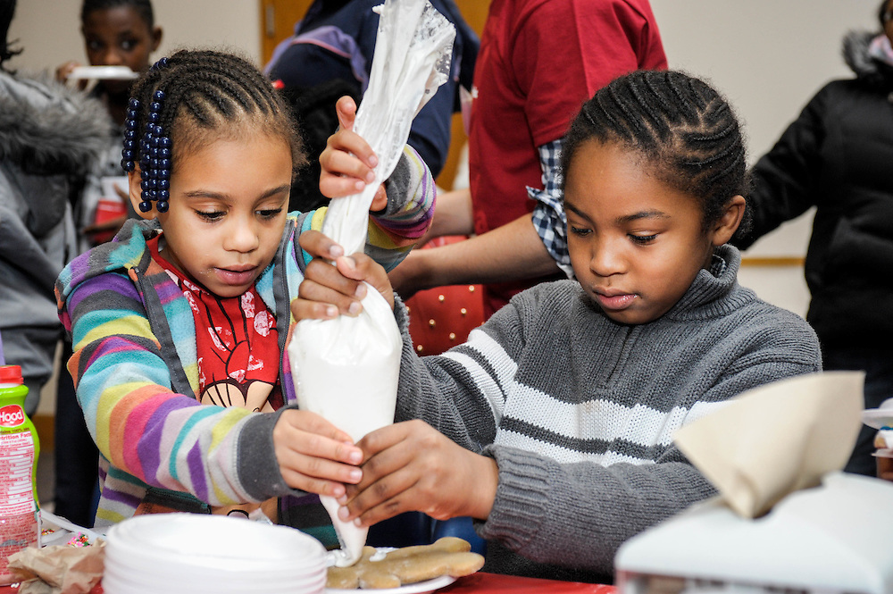 Two children decorate a gingerbread man at hte Goodwill Holiday PArty at the Goodwill Headquarters in Roxbury, MA.
