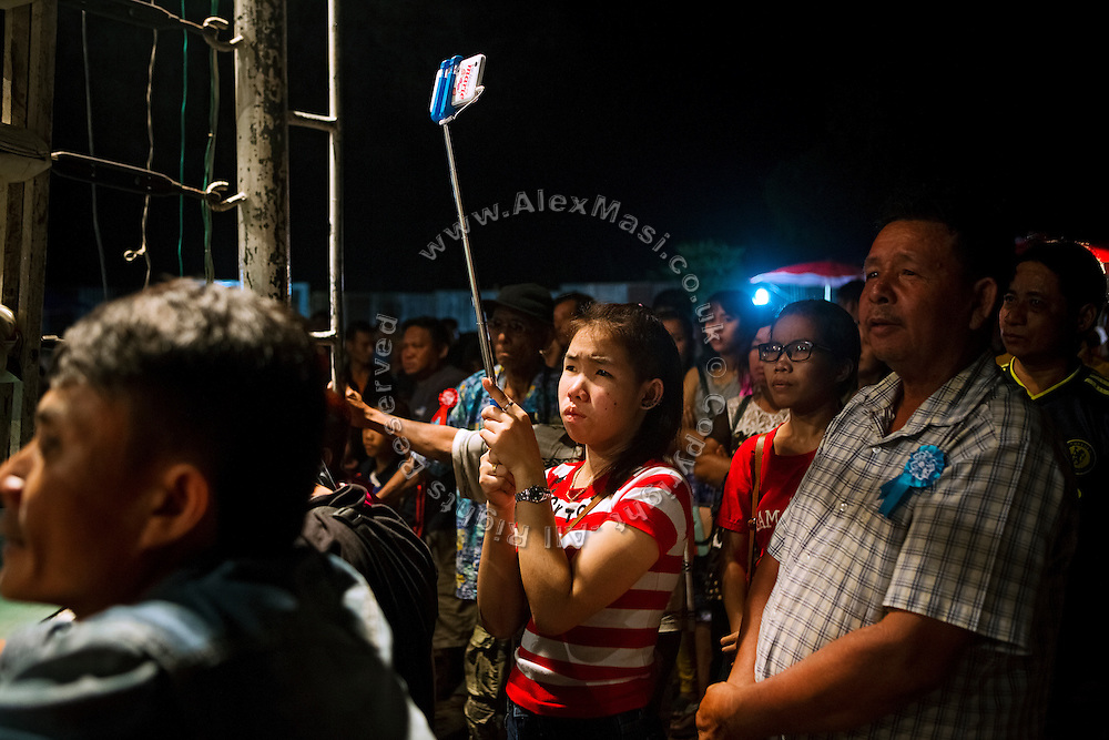 A young woman is recording a Muay Thai boxing match on her mobile phone and selfie stick, while attending an event organised in a village near Ubon Ratchathani, northeast Thailand.