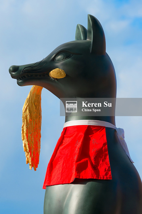 Bronze sculpture of fox holding rice ears in mouth in Fushimi Inari Shrine, Kyoto, Japan