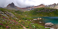 The beautiful turquoise waters of Ice Lake near Silverton, Colorado glow even in the shade of the clouds