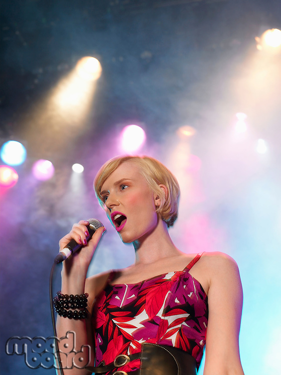 Young Woman Singing in Concert on stage low angle view