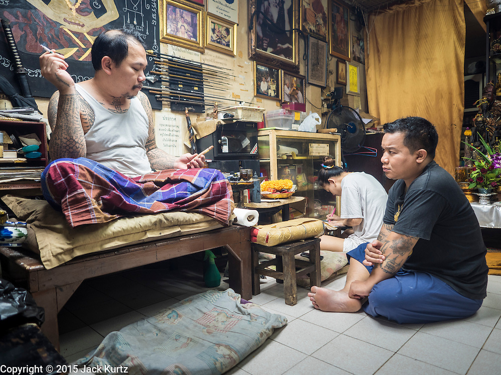 "27 MAY 2015 - BANGKOK, THAILAND:  AJARN NENG ONNUT, a revered tattoo artist in Bangkok, talks to his assistants before he starts tattooing people in his Bangkok home. Sak Yant (Thai for ""tattoos of mystical drawings"" sak=tattoo, yantra=mystical drawing) tattoos are popular throughout Thailand, Cambodia, Laos and Myanmar. The tattoos are believed to impart magical powers to the people who have them. People get the tattoos to address specific needs. For example, a business person would get a tattoo to make his business successful, and a soldier would get a tattoo to help him in battle. The tattoos are blessed by monks or people who have magical powers. Ajarn Neng, a revered tattoo master in Bangkok, uses stainless steel needles to tattoo, other tattoo masters use bamboo needles. The tattoos are growing in popularity with tourists, but Thai religious leaders try to discourage tattoo masters from giving tourists tattoos for ornamental reasons.    PHOTO BY JACK KURTZ"