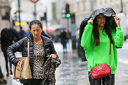 © Licensed to London News Pictures. 27/09/2019. London, UK. A woman on Regents Street covers her head during rain and wet weather. According to the Met Office, this weekend is set to be washout with over 2o hours of rainfall in the capital. Photo credit: Dinendra Haria/LNP