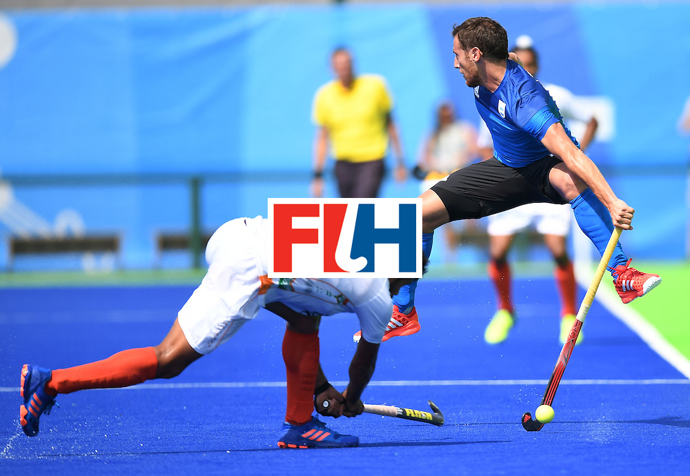 Argentina's Lucas Vila jumpas as India's Harmanpreet Singh hits the ball during the men's field hockey Argentina vs India match of the Rio 2016 Olympics Games at the Olympic Hockey Centre in Rio de Janeiro on August, 9 2016. / AFP / MANAN VATSYAYANA        (Photo credit should read MANAN VATSYAYANA/AFP/Getty Images)