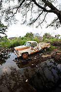 A rusted out truck rest in a rain puddle in the lower 9th ward of New Orleans one year after Hurricane Katrina.