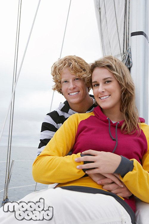 Young couple smiling on sailboat, portrait
