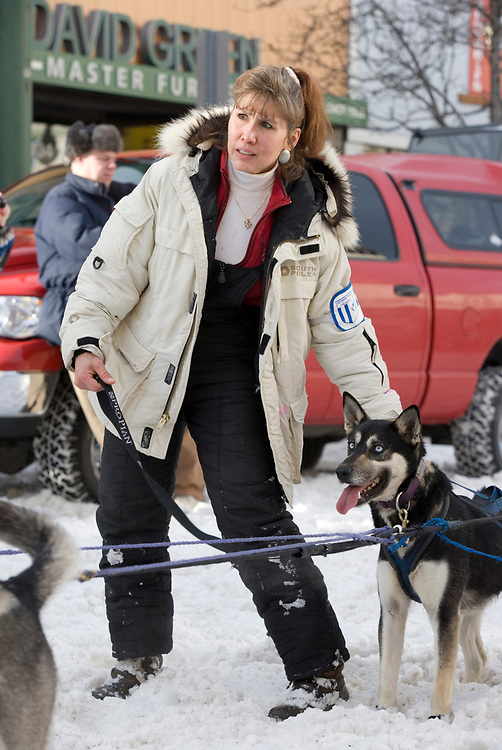 USA, Alaska, Anchorage, Handler holds dog team's leads in snow along 4th Avenue in anticipation of start of 2005 Iditarod sled dog race