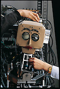 Researchers adjust the mechanism of WE-3RIII, Waseda University's head robot, after it accidentally whiplashed into its own wires. In a situation all too familiar to robotics researchers, Atsuo Takanishi ( hand on right) is trying to make his creation work. His research team's robot, WE-3RIII (Waseda Eye Number 3 Refined Version III) can follow a light with its digital-camera eyes, moving its head if needed. In the laboratory the robot worked perfectly, its movements almost disconcertingly lifelike. But while being installed at a robot exhibit in Tokyo, WE-3RIII inexplicably and violently threw back its head, tearing apart its own wiring. Now Takanishi and one of his students (hand on left) are puzzling over the problem and will solve it only in the early hours of the morning before the exhibit opened. Japan. From the book Robo sapiens: Evolution of a New Species, page 233.