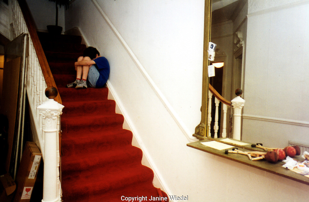 Depressed child huddled sitting on staircase hiding from the world.