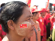 01 NOVEMBER 2015 - YANGON, MYANMAR: A woman with NLD stickers on her face at the NLD's last election rally of the 2015  election in the Yangon suburbs Sunday. Political parties are wrapping up their campaigns in Myanmar (Burma). National elections are scheduled for Sunday Nov. 8. The two principal parties are the National League for Democracy (NLD), the party of democracy icon and Nobel Peace Prize winner Aung San Suu Kyi, and the ruling Union Solidarity and Development Party (USDP), led by incumbent President Thein Sein. There are more than 30 parties campaigning for national and local offices.    PHOTO BY JACK KURTZ