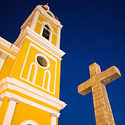 """There has been a church on this spot since about 1525, but it was destroyed and rebuilt several times in the following centuries as the city of Granada was attacked by pirates and others. Construction on the current version began in 1888 but was not fully completed until 1972. With its distinctive yellow with white trim exterior, it stands over Parque Central in the heart of Granada, Nicaragua. The cross was installed in 1901 and is made of basalt. At the top the inscription INRI is read, and a chalice and a bunch of grapes symbolizing the blood of Christ . In the center, where the arms are crossed, the X and P interlaced letters: monogrammed initials Redeemer. On the left arm, there are four quadrangles, with a cross in the center of each- symbolizing the four Gospels . On the right arm, two arms entwined, symbol of the union of Christ with humanity. At the foot of the cross, there is a skull on two femurs crossed to represent the bones of Adam , finally-in the base-, bears the inscription """"Jesus Christ God, man lives, reigns and rules""""."""