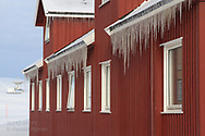 Building bedecked in April icicles frames distant VLBI radio telescope at the international science village of Ny-Alesund on Spitsbergen island in Kongsfjorden; Svalbard, Norway.