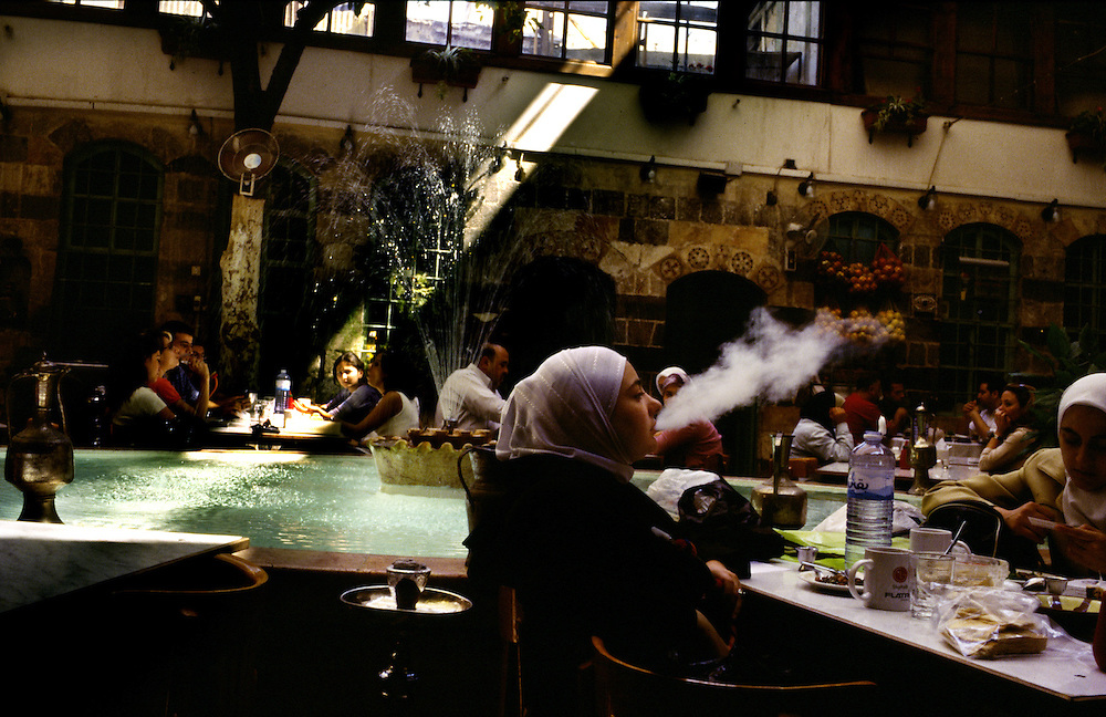 Syria, a young girl smokes a water pipe with friends in a coffee in Damascus.