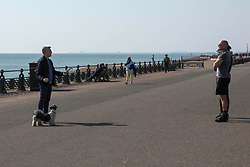 People engage in conversation while adhering to the Government's advice of keeping 2 metres away from each other while on the seafront in Brighton, East Sussex, as the UK continues in lockdown to help curb the spread of Coronavirus.