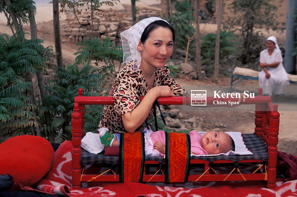 Uighur woman with a child in cradle, Kashgar, Xinjiang Province, Silk Road, China