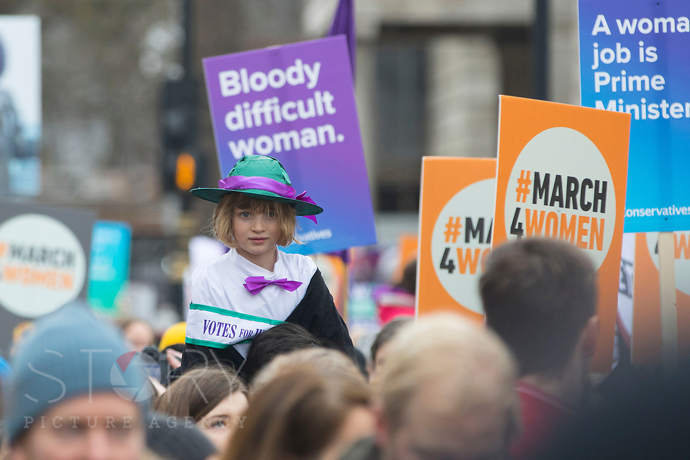 UNITED KINGDOM, London: 04 March 2018 Florence Wickendon, aged 7 and dressed as a suffragette, joins thousands of supporters on Whitehall during the #March4Women rally through London this afternoon. Thousands of people marched from Parliament to Trafalgar Square to celebrate International Women's Day and 100 years since the first women in the UK gained the right to vote. <br /> Rick Findler / Story Picture Agency