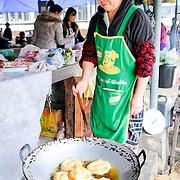 A woman cooks fried dough in a large wok at the morning market in Sam Neua (also spelled Samneua, Xamneua and Xam Neua) in northeastern Laos.