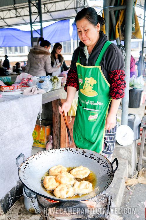 A woman cooks fried dough in a large wok at the morning market in Sam Neua (also spelled Samneua, Xamneua and Xam Neua) in northeastern Laos.