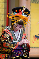 A female performer dressed in traditional geisha outfit performs on stage at this theme park devoted to Edo period Japan.