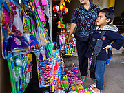 03 AUGUST 2017 - SUKAWATI, BALI, INDONESIA: A boy looks at toys for sale in the market in Sukawati. Bali's local markets are open on an every three day rotating schedule because venders travel from town to town. Before modern refrigeration and convenience stores became common place on Bali, markets were thriving community gatherings. Fewer people shop at markets now as more and more consumers go to convenience stores and more families have refrigerators.    PHOTO BY JACK KURTZ