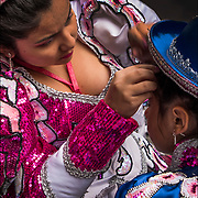 Portrait of Bolivian dancers. mother helps daughter with hair and make up  before the 11th Annual Dance Parade in NYC.
