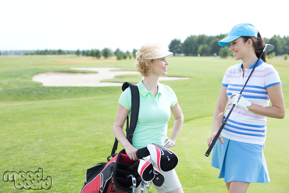 Smiling female golfers talking at golf course