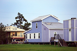 20 August 2015. New Orleans, Louisiana. <br /> Hurricane Katrina revisited. <br /> A cluster of brightly coloured 'Make it Right' homes inspired by actor Brad Pitt have sprung up in a limited area. A decade after the storm and recovery remains largely elusive for most of the area hardest hit by Katrina. <br /> Photo credit©; Charlie Varley/varleypix.com.