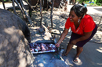 Guarani woman cooking goat meat in mud brick oven