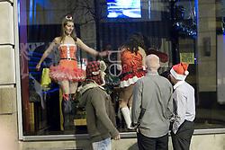 "© licensed to London News Pictures. Manchester, UK 17/12/2011. Ladies in Santa costumes dance in the window of a nightclub as partygoers outside look on. Despite freezing temperatures, ""Mad Friday"" revellers in Manchester enjoy what is traditionally the busiest night of the year for emergency services, before Christmas. Photo credit: Joel Goodman/LNP"