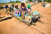 29 JUNE 2013 - BATTAMBANG, CAMBODIA:  Cambodians use a bamboo train to go home after a day of shopping in a local market. The bamboo train, called a norry (nori) in Khmer is a 3m-long wood frame, covered lengthwise with slats made of ultra-light bamboo, that rests on two barbell-like bogies, the aft one connected by fan belts to a 6HP gasoline engine. The train runs on tracks originally laid by the French when Cambodia was a French colony. Years of war and neglect have made the tracks unsafe for regular trains.  Cambodians put 10 or 15 people on each one or up to three tonnes of rice and supplies. They cruise at about 15km/h. The Bamboo Train is very popular with tourists and now most of the trains around Battambang will only take tourists, who will pay a lot more than Cambodians can, to ride the train.       PHOTO BY JACK KURTZ