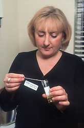 Female doctor examining urine test sample,