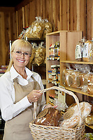 Portrait of a happy senior employee holding bread basket in grocery store
