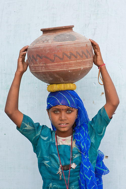 Young and beautiful Rajasthani girl carrying traditional waterpot in India's dry Thar desert.