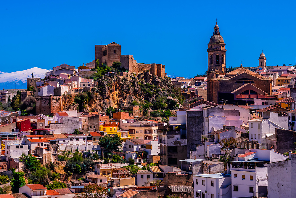 High angle view of the town of Loja, Granada Province, Andalusia, Spain with snow capped mountains in the background.